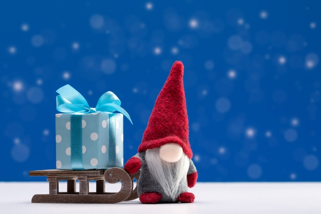 크리스마스 배경입니다. 빨간 모자에있는 그놈은 썰매에 명절 선물 상자를 들고있다