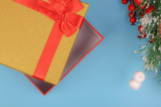 Christmas background. gold glitter gift box with bow on a blue background. empty space for text, top view, flat lay
