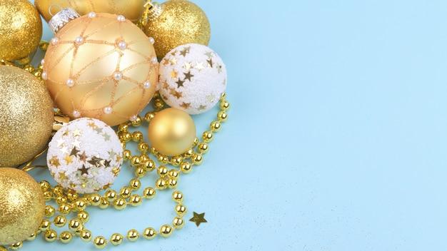 Новогодний фон с золотыми елочными шарами и золотым декором на синем пастельном фоне