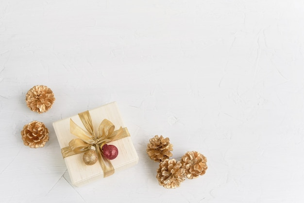 크리스마스 배경입니다. 흰색 바탕에 황금 리본으로 장식된 황금 크리스마스 장식과 선물 또는 선물 상자. 상위 뷰, 복사 공간입니다.