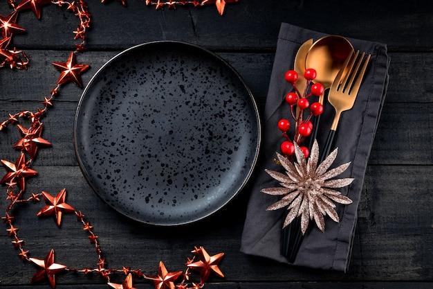 クリスマスの背景-リネンナプキンの金色のカトラリーと黒い木製の背景の黒い空のプレート、テキスト用の空きスペース。新年のサービングオプション。