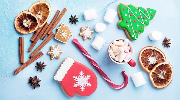 Рождественский фон. группа пряников, корицы, апельсина, игрушек и чашки горячего шоколада на голубом фоне. выборочный фокус. вид сверху. копировать пространство