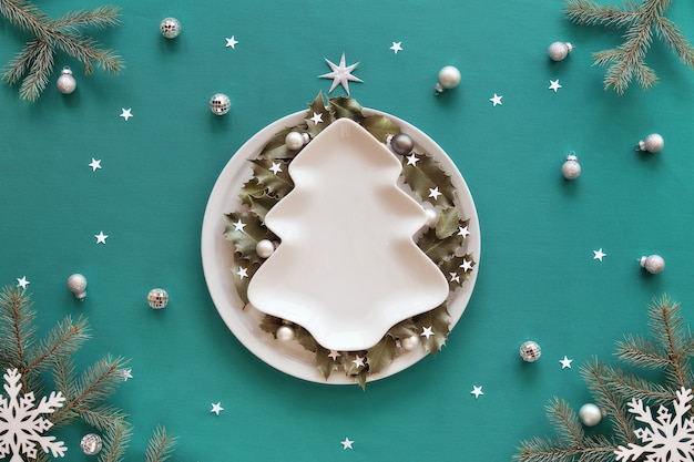 Новогодний фон в зеленом и белом. xmas tree shape пластина с копией пространства на столе, покрытом зеленой мятой. веточки ели и белые украшения. холли уходит на круглую тарелку.