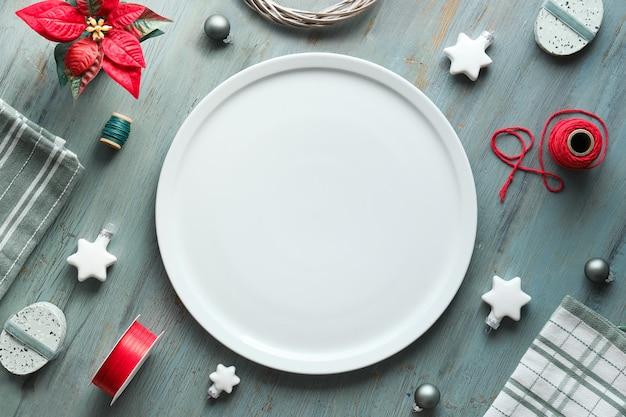 グレー、赤、白のクリスマス背景。テキストスペース、大きなプレート上のコピースペース。灰色の織り目加工の木材、幾何学的なフラットレイアウト、赤いポインセチア、白い星、繊維、綿の配置のトップビュー