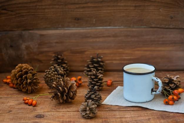 소박한 스타일의 크리스마스 배경입니다. 뜨거운 우유 차가 든 금속 머그는 소나무 콘, 가문비나무 가지, 밀 이삭과 로즈힙 사이의 나무 표면에 식탁보 위에 서 있습니다. 복사 공간, 플랫 레이