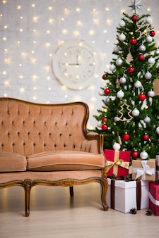 Christmas background - interior with christmas tree, vintage sofa and gift boxes