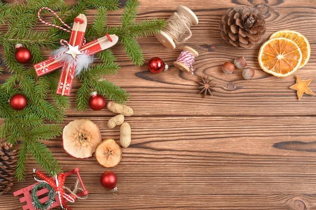 モミの枝、おもちゃ、エコ装飾で作られたクリスマスの背景。年末年始のナチュラルなデザイン。クリスマスと新年のグリーティングカード。スペースをコピーします。フラットレイ、上面図。