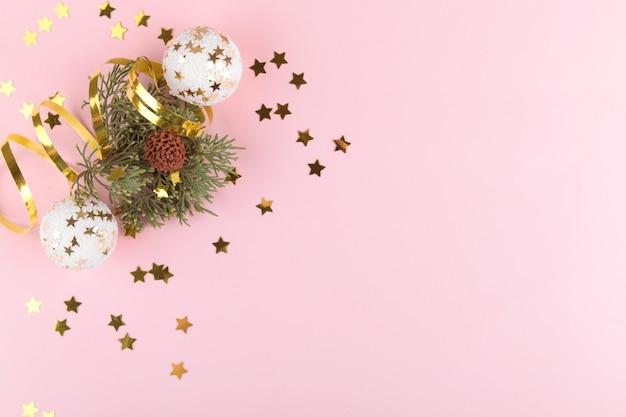 クリスマスの背景。ピンクのパステルカラーの背景にゴールドのクリスマスボールと金色の装飾が施された自然なモミの木の枝