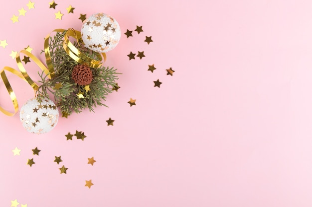 Christmas background. natural fir tree branches with gold christmas balls and golden decortation on pink pastel background