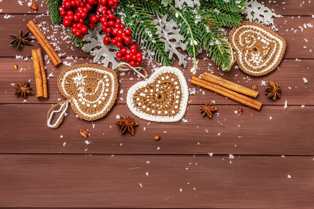 Christmas background. new year fir tree, dog rose, fresh leaves, crocheted ginger cookies hearts, spices and artificial snow.