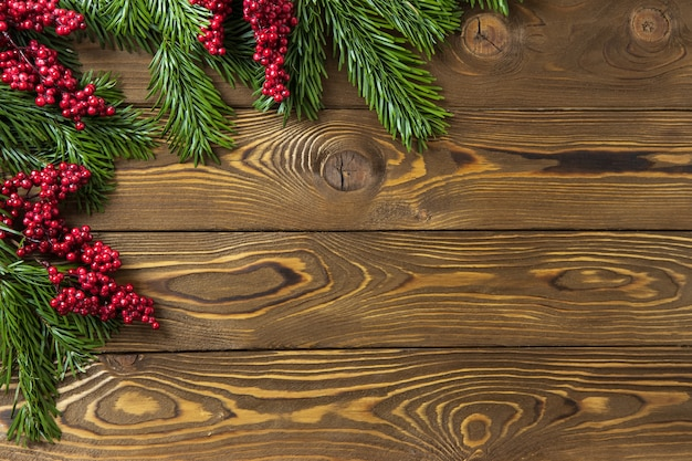 Christmas background nobilis fir branches twigs with red berries on brown wooden planks