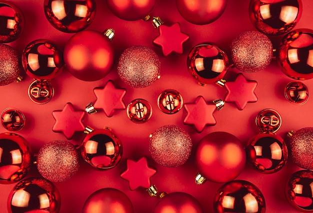 Новогодний фон из красных шаров, серпантина и звезд на красном фоне. плоская планировка, вид сверху.