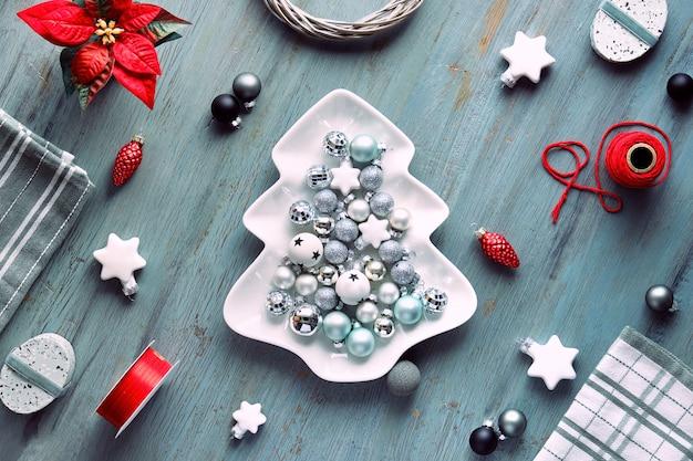 Новогодний фон на темно-сером дереве в белых и красных тонах. тарелка в форме елки с шарами, геометрическая плоская кладка с игрушками, цветами, подарочными коробками.