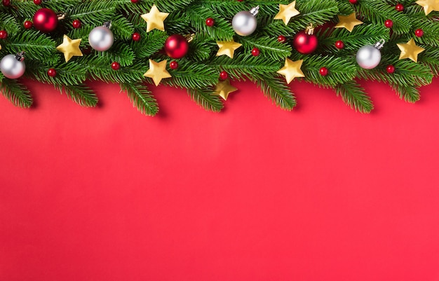 クリスマスの背景はグリーティングカードの頭上の緑のモミの木の枝と装飾を提示します