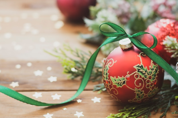Christmas background. red beautiful bauble with green ribbon, fir branches.