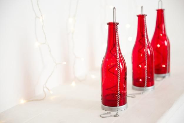 クリスマスの背景。中に花輪が付いた赤いボトル、白い背景の上に立つ