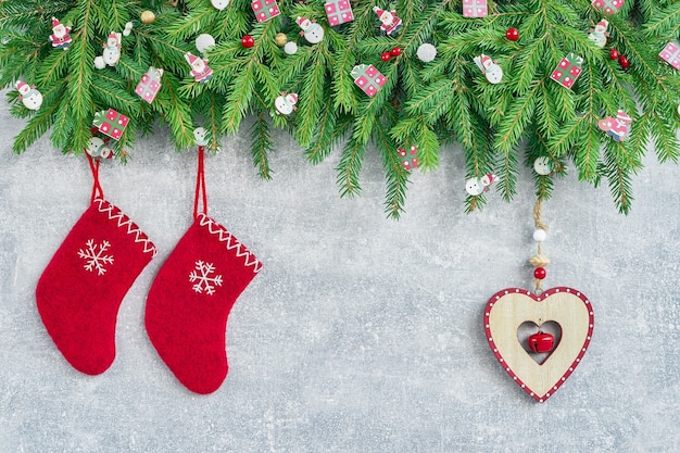 크리스마스 배경입니다. 회색 배경에 크리스마스 나무 가지가 있는 빨간 크리스마스 양말과 심장. 복사 공간, 평면도.
