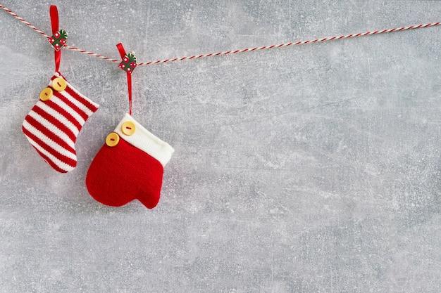 Рождественский фон красные рождественские носки и варежки на сером