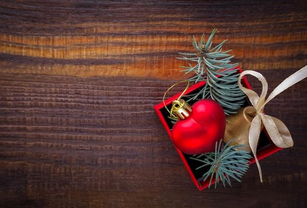 Новогодний фон: красная подарочная коробка с елочной игрушкой в форме сердца, золотой колокольчик и еловые ветки
