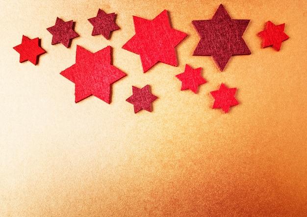 クリスマスの背景。金色の紙に赤い星。上面図、フラットレイ