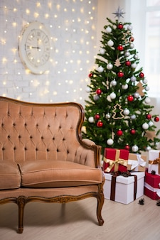 Christmas background - room with decorated christmas tree, vintage sofa, lights and gift boxes