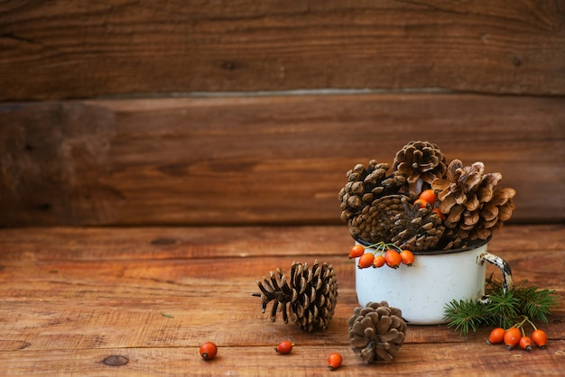 Christmas background in rustic style. atmospheric composition of pine cones in vintage cup, rosehips berries, spruce branches and wheat spikelets is placed on wooden surface. copyspace, flat lay