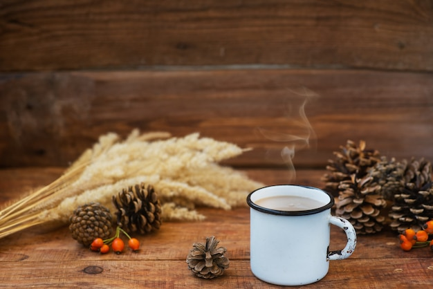 Christmas background in rustic style. a metal mug with hot milk tea stands on a tablecloth, on a wooden surface among pine cones, spruce branches, spikelets of wheat and rosehips. copy space, flat lay