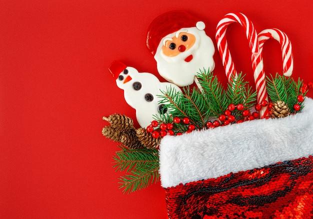 Рождественский фон. шляпа санты с конфетами и украшениями на красном. вид сверху, копировать пространство
