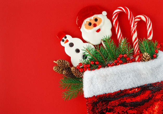 Christmas background. santa hat with candies and decorations on red. top view,copy space