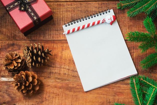 Рождественский фон. еловые ветки, подарок, шишки и блокнот с ручкой на деревянном фоне