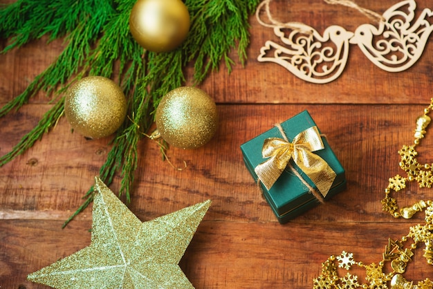 Christmas background. spruce branches, gift, wooden bird figures and golden star on a wooden background. copy space