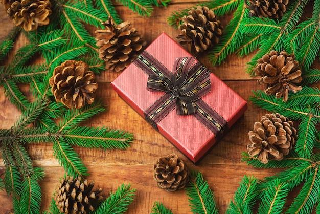 Рождественский фон. еловые ветки в виде круглой рамки, шишки и подарок посередине