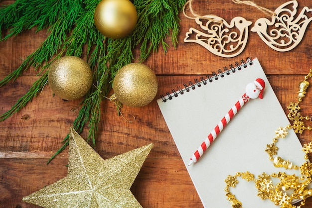 Christmas background. spruce branches, notebook, wooden bird figures and golden star on a wooden background. . copy space. top view. christmas or new year's card. place for text, flat lay