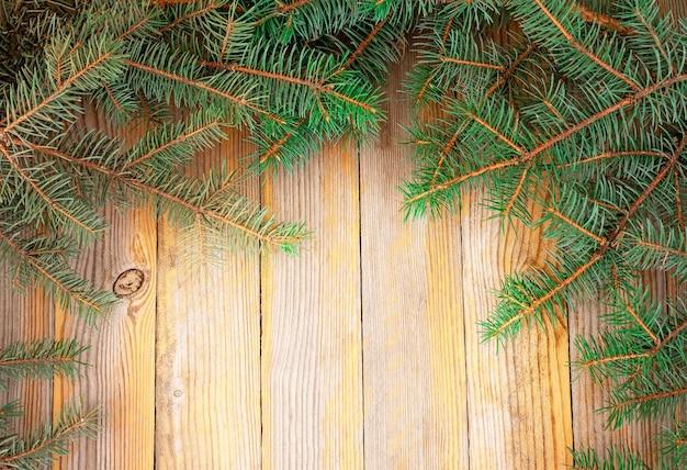 Рождественский фон. еловые ветки на деревянной доске. вид сверху
