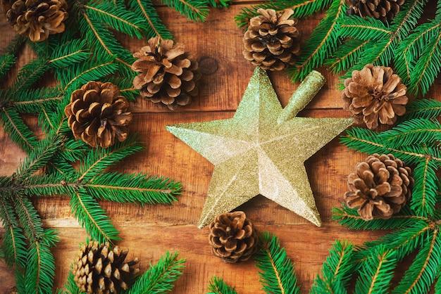 Рождественский фон. еловые ветки, шишки и звезда посередине на деревянном фоне