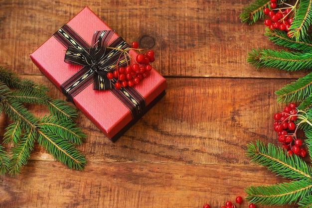Рождественский фон. еловые ветки, красные ягоды калия и подарок на деревянном фоне