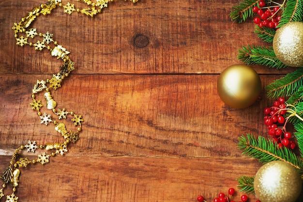 Рождественский фон. еловые ветки, красные ягоды калия и яркие новогодние шары на деревянном фоне. вид сверху. рождественская или новогодняя открытка. место для текста, место для копирования, плоская планировка