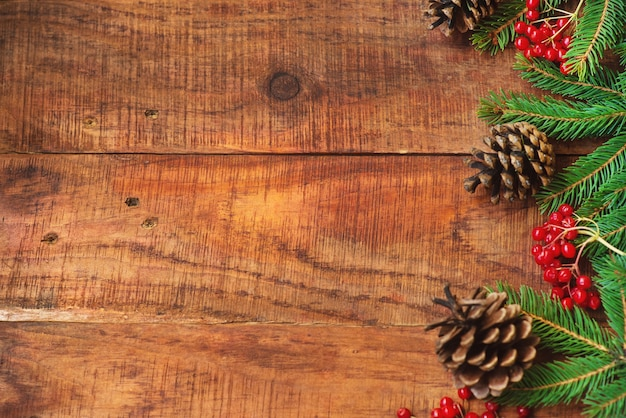 Рождественский фон. еловые ветки, красные ягоды калия и сосновые шишки на деревянном фоне. вид сверху. рождественская или новогодняя открытка. место для текста, место для копирования, плоская планировка