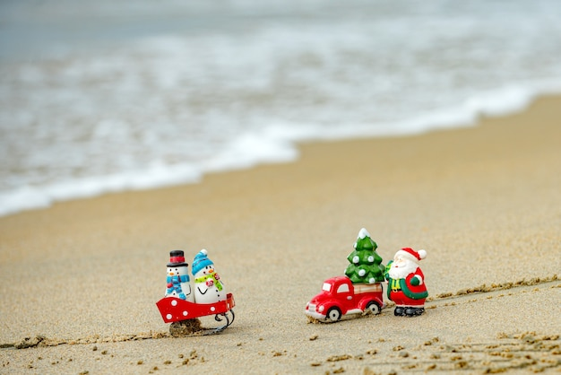 Christmas background. toy santa and snowman on summer beach, concept for travel in hot countries.