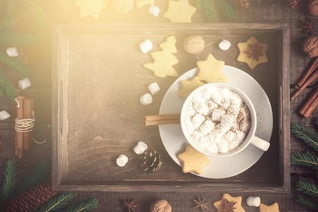 크리스마스 배경입니다. 계피와 마시멜로로 장식된 코코아와 쿠키가 있는 트레이. 톤