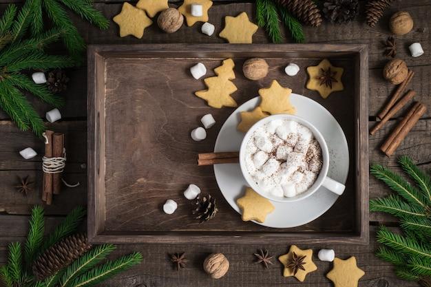 크리스마스 배경입니다. 계피와 마시멜로로 장식된 코코아와 쿠키가 있는 트레이.