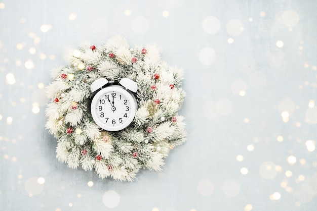 Christmas background. white christmas wreath and alarm clock on blue background. copy space for text