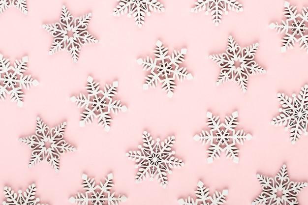 Рождественский фон. белые снежные украшения на розовом фоне.