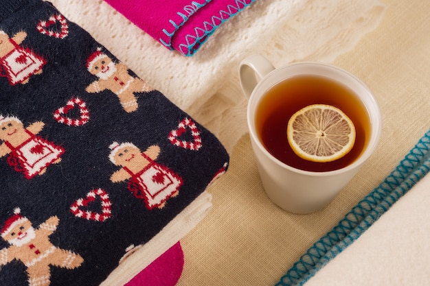 Christmas background winter clothes with traditional patterns and hot tea with lemon