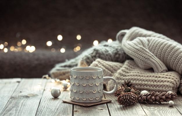 美しいカップ、ニットの要素、ボケ味のぼやけた背景の装飾的な詳細を持つクリスマスの背景。