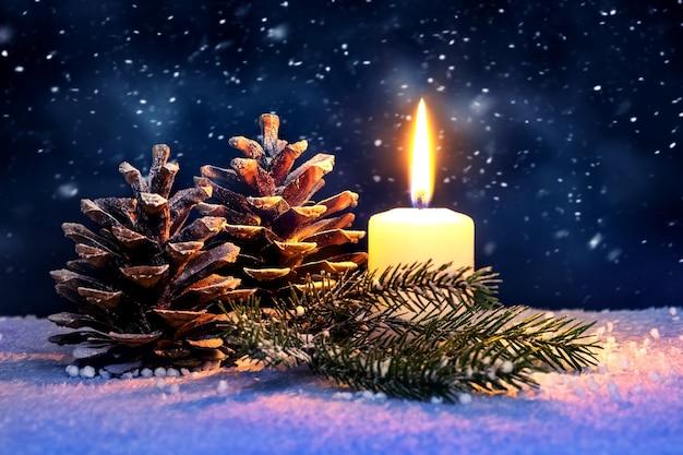 Новогодний фон со свечой и шишками на темном фоне во время снегопада