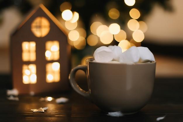 Новогодний фон с чашкой кофе с зефиром при свете боке