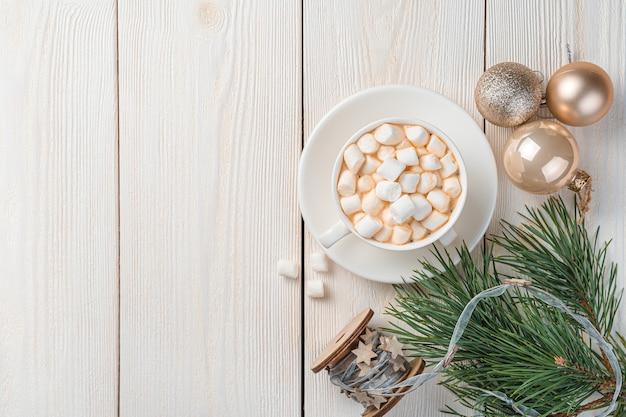 マシュマロ、モミのボール、松の枝とコーヒーのカップとクリスマスの背景。上面図、コピースペース。