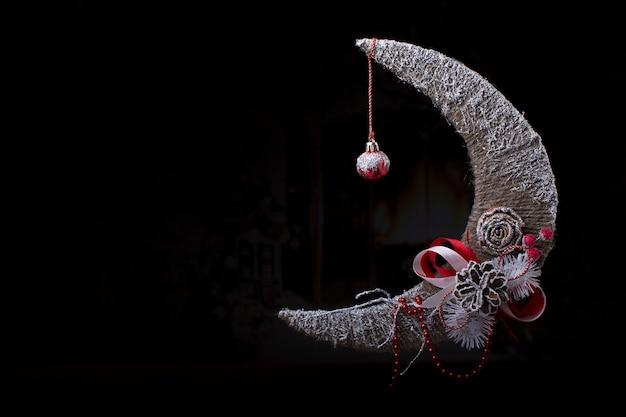 Новогодний фон с месяцем елочная игрушка с конусом на черном фоне