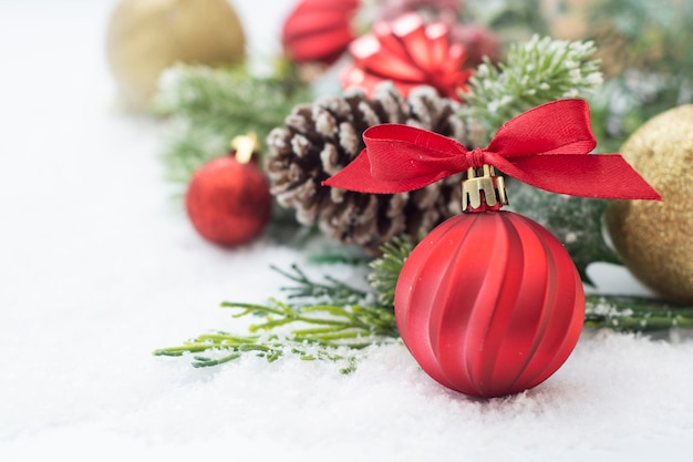 Christmas background with baubles, green fir branches, pine cones, on white snow background.
